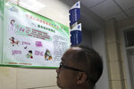 A visitor to a hospital looks at a poster with information on rabies vaccine in Beijing, China, Monday, July 23, 2018. China's No. 2 leader has ordered an investigation of its vaccine industry after violations by a rabies vaccine producer prompted a public outcry following scandals over shoddy drugs and food. (AP Photo/Ng Han Guan)