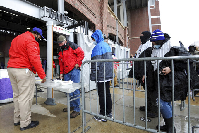 Fans prepare to go through a metal detector prior to an NFL football game between the Baltimore Ravens and the Pittsburgh Steelers, Sunday, Nov. 1, 2020, in Baltimore. A limited number of fans were allowed to attend the game at M&T Bank Stadium for the first time during the season under COVID-19 restrictions. (AP Photo/Gail Burton)