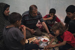 Zaki and Jawaher Nassir have dinner with their sons in an apartment they rented after their house was heavily damaged by airstrikes in Beit Hanoun, northern Gaza Strip, Monday, June 21, 2021. (AP Photo/Felipe Dana)