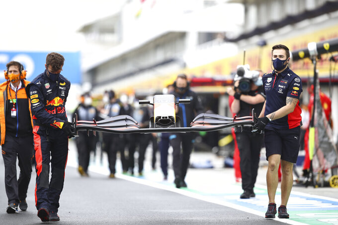 Mechanics of Red Bull driver Max Verstappen of the Netherlands carry a front car piece prior the the Hungarian Formula One Grand Prix race at the Hungaroring racetrack in Mogyorod, Hungary, Sunday, July 19, 2020. (Mark Thompson/Pool via AP)