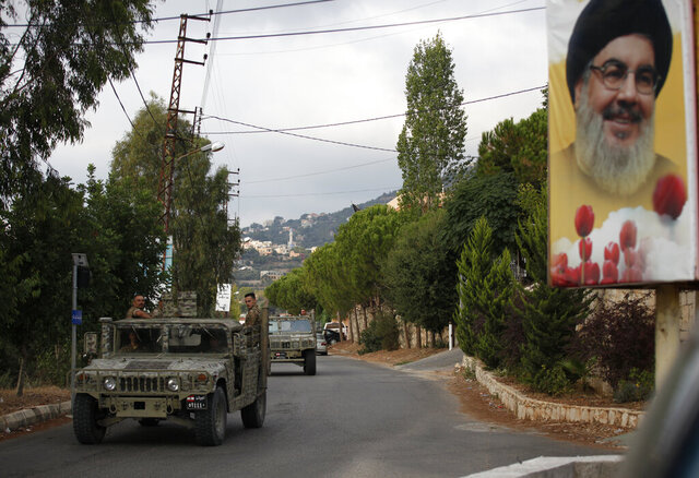 Lebanese army vehicles pass next to a portrait of Hezbollah leader Sayyed Hassan Nasrallah, as they patrol on a road that leads to the site of an explosion that rocked a Hezbollah stronghold, in the southern village of Ain Qana, Lebanon, Tuesday, Sept. 22, 2020. The powerful explosion sent thick grey smoke billowing over the village, but the cause was not clear. (AP Photo/Mohammed Zaatari)