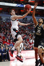 Louisville guard Ryan McMahon (30) shoots a reverse layup as he's defended by Wake Forest center Olivier Sarr (30) during the first half of an NCAA college basketball game Wednesday, Feb. 5, 2020, in Louisville, Ky. (AP Photo/Wade Payne)