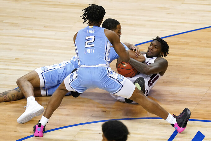 Virginia Tech guard Tyrece Radford, right, tries to protect the ball as North Carolina guard Caleb Love (2) and teammate forward Garrison Brooks, middle, defend during the first half of an NCAA college basketball game in the quarterfinal round of the Atlantic Coast Conference tournament in Greensboro, N.C., Thursday, March 11, 2021. (AP Photo/Gerry Broome)