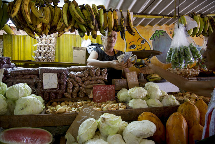 Olga Castillo counts the change after selling vegetables to a customer at her stall in Havana, Cuba, Wednesday, July 30, 2019. The Cuban government is capping prices for food and beverages throughout the country in order to control the risk of inflation due to a state wage hike and stagnant productivity. (AP Photo/Ismael Francisco)