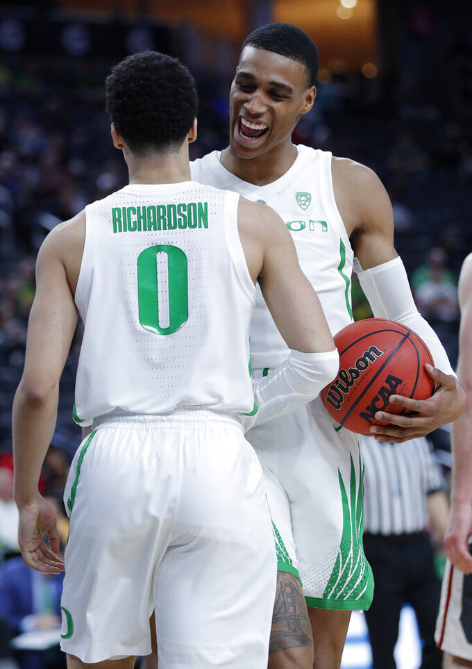 Oregon's Kenny Wooten, right, and Oregon's Will Richardson celebrate after a play against Washington State during the second half of an NCAA college basketball game in the first round of the Pac-12 men's tournament Wednesday, March 13, 2019, in Las Vegas. (AP Photo/John Locher)