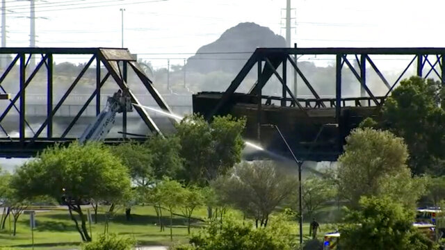 FILE - In this July 29, 2020, file photo, smoke fills the sky at the scene of a train derailment in Tempe, Ariz. The FBI found no evidence of criminal activity in the July 29 freight train derailment and fire that extensively damaged a century-old railroad bridge in metro Phoenix. That's according to a National Transportation Safety Board preliminary report that did not identify a probable cause for the derailment of 12 cars. (AP Photo/Pool, File)