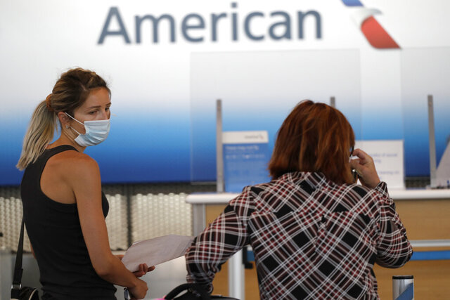 In this June 16, 2020 file photo travelers wear masks as they wait at the American Airlines ticket counter at O'Hare International Airport in Chicago. American Airlines has banned a man who was kicked off a plane for refusing to wear a face covering, among the first such incidents since airlines promised this week to step up enforcement of their mask rules. A spokesman for American said Thursday, June 18, 2020 that the airline decided to ban the man after reviewing the incident, which occurred Wednesday at New York's LaGuardia Airport. (AP Photo/Nam Y. Huh)