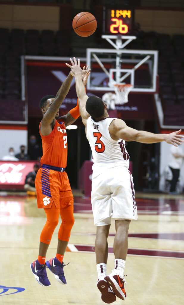 Clemson's Al-Amir Dawes, left,  shoots a 3-point basket over Virginia Tech's Wabissa Bede (3) in the second half of an NCAA  college basketball game in Blacksburg Va., Tuesday, Dec. 15, 2020.  (Matt Gentry/The Roanoke Times via AP, Pool)