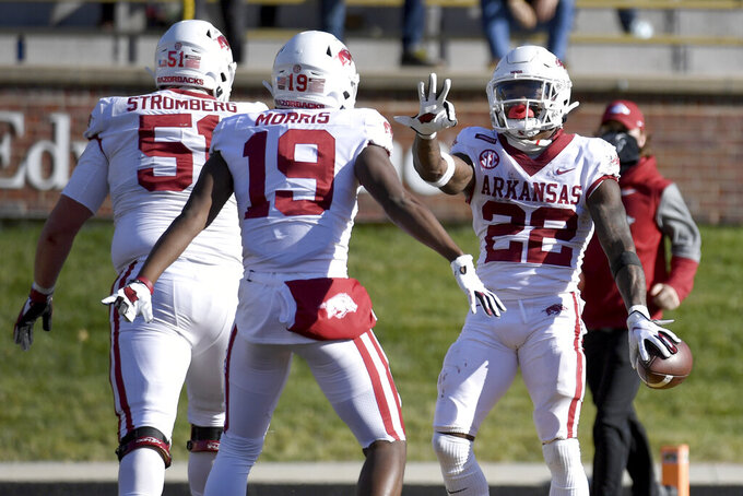 Arkansas running back Trelon Smith (22) is congratulated by teammate Tyson Morris (19) after scoring during the second half of an NCAA college football game against Missouri Saturday, Dec. 5, 2020, in Columbia, Mo. (AP Photo/L.G. Patterson)