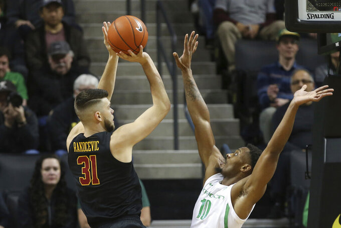 Southern California's Nick Rakocevic, left, shots over Oregon's Shakur Juiston during the first half of an NCAA basketball game in Eugene, Ore., Thursday, Jan. 23, 2020. (AP Photo/Chris Pietsch)