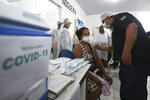 A woman of the Ticuna Indigenous group gets her shot of the COVID-19 vaccine produced by China's Sinovac Biotech Ltd, during the start of the vaccination plan on indigenous lands at the Ticuna de Umariaçu village health post in Tabatinga, Amazonas state, Brazil, Tuesday, Jan. 19, 2021. (AP Photo/Andre Borges)