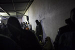 FILE - In this Nov. 29, 2013, file photo African migrants wait in a barrack at a detention center for illegal migrants in Abu Salim district on the outskirts of Tripoli, Libya. The United Nations opened its