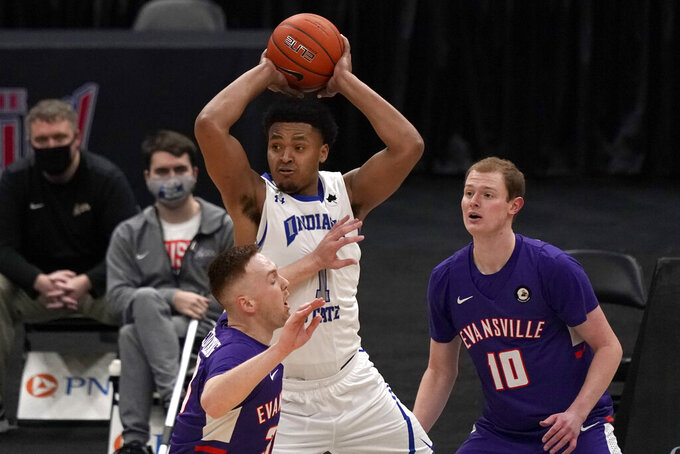 Indiana State's Tre Williams, center, looks to pass as Evansville's Noah Frederking and Evan Kuhlman (10) defend during the first half of an NCAA college basketball game in the quarterfinal round of the Missouri Valley Conference men's tournament Friday, March 5, 2021, in St. Louis. (AP Photo/Jeff Roberson)