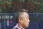 A man walks by an electronic stock board of a securities firm in Tokyo, Tuesday, Oct. 1, 2019. Shares rose in Asia on Tuesday, with markets in Hong Kong and Shanghai closed for a national day holiday. (AP Photo/Koji Sasahara)