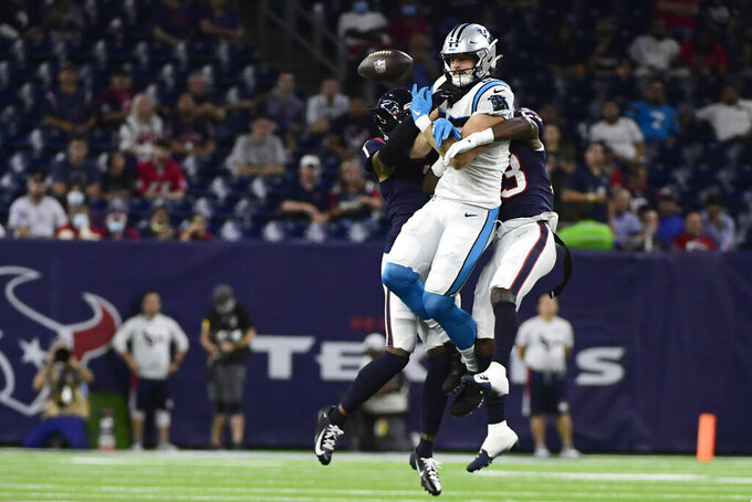 Carolina Panthers tight end Dan Arnold, center, tries to make a catch as Houston Texans' Lonnie Johnson Jr. (1) and Eric Murray (23) defend during the first half of an NFL football game Thursday, Sept. 23, 2021, in Houston. (AP Photo/Justin Rex)