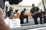 Former Jacksonville Jaguars NFL football player Ernest Wilford, right, now a member of the Jacksonville Sheriff's Office, leads the Jaguars protest group to take a knee during a moment of silence on the steps of the Jacksonville Sheriff's Office headquarters,  Friday morning, June 5, 2020, in Jacksonville, Fla., as they protest against inequality and police brutality. (Bob Self/The Florida Times-Union via AP)