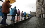 People walk on catwalk set up on the occasion of a high tide, in a flooded Venice, Italy, Tuesday, Nov. 12, 2019. The high tide reached a peak of 127cm (4.1ft) at 10:35am while an even higher level of 140cm(4.6ft) was predicted for later Tuesday evening. (AP Photo/Luca Bruno)