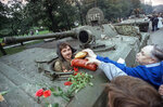 FILE - In this Wednesday, Aug. 21, 1991 file photo, appreciative Muscovites hand bread, sausages and flowers to a Soviet tank's driver who helped stop the failed hardline coup in Moscow, Russia.The August 1991 coup that briefly ousted Soviet leader Mikhail Gorbachev collapsed in just three days, precipitating the breakup of the Soviet Union that plotters said they were trying to prevent. (AP Photo/Czarek Sokolowski, File)