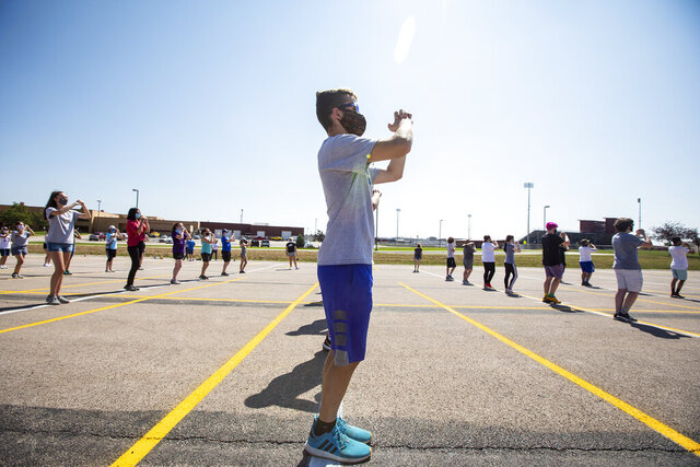 Thunder Basin High School senior Brian Jackson marches in line with classmates as the school's marching band preps for the upcoming season during a morning band camp session in Gillette, Wyo., on Wednesday, Aug. 5, 2020. The coronavirus pandemic has the local high school musicians marching to a different drummer.   (Mike Moore/Gillette News Record via AP)