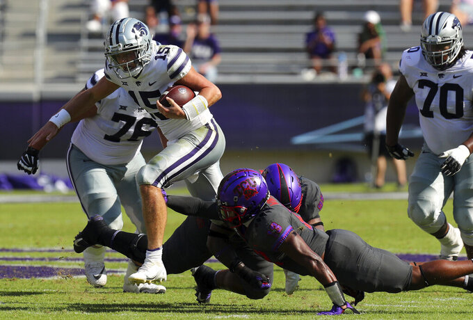 Kansas State quarterback Will Howard (15) carries the ball as he tries to evade TCU linebacker Dee Winters (13) in the first quarter of an NCAA college football game Saturday, Oct. 10, 2020, in Arlington, Texas. (AP Photo/Richard W. Rodriguez)