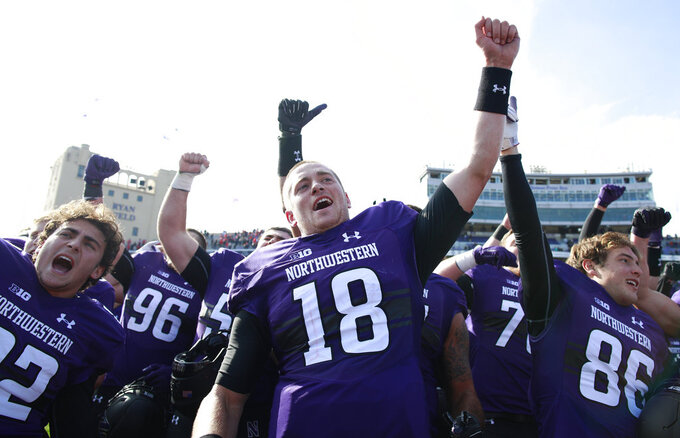 Northwestern's, from left, Alex Oelsner, Clayton Thorson (18), and Raymond Niro III cheer as they celebrate their team's win over Nebraska in an NCAA college football game Saturday, Oct. 13, 2018, in Evanston, Ill. (AP Photo/Jim Young)
