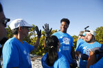 Arizona Cardinals running back Kenyan Drake high fives another Huddle for 100 beach clean up crew member at the Historic Virginia Key Beach Park on Tuesday, Jan. 28, 2020, in Miami.  Climate change poses a threat to South Florida's way of life, including Miami's customary spot in the NFL's Super Bowl rotation. The game will be played Sunday in Miami for the 11th time, the most of any city. But the sea and temperature are rising, which could eventually make South Florida an unsuitable Super Bowl site. (AP Photo/Brynn Anderson)