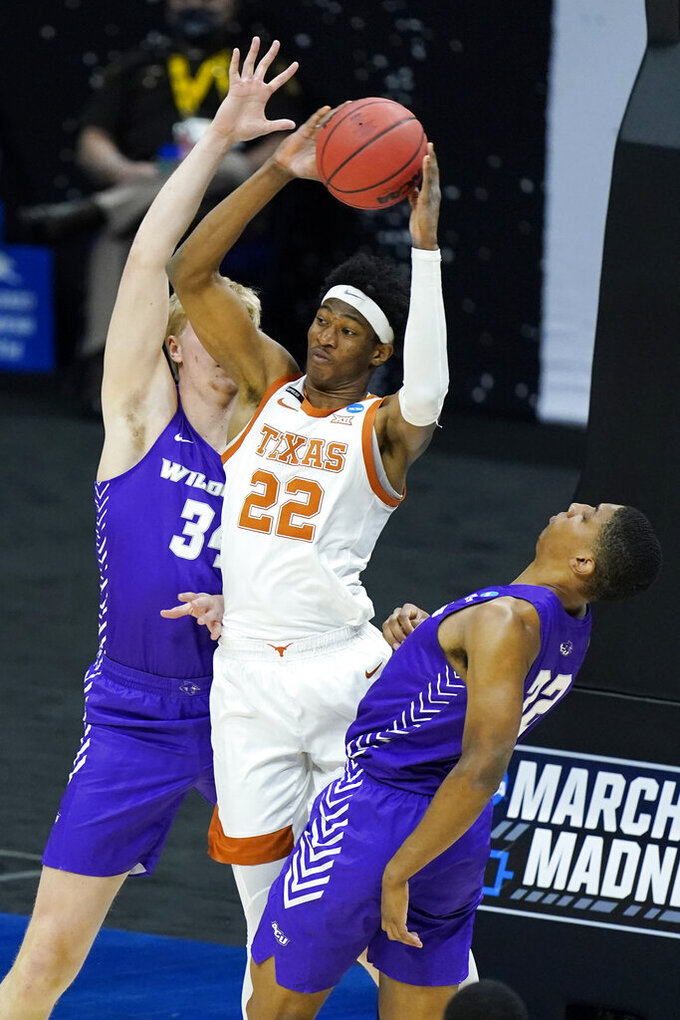 Texas' Kai Jones (22) passes the ball away from Abilene Christian's Kolton Kohl (34) and Joe Pleasant (32) during the first half of a college basketball game in the first round of the NCAA tournament at Lucas Oil Stadium in Indianapolis Saturday, March 20, 2021. (AP Photo/Mark Humphrey)