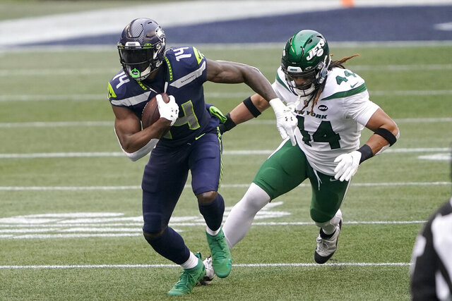 Seattle Seahawks wide receiver DK Metcalf (14) runs with the ball as New York Jets inside linebacker Harvey Langi gives chase during the first half of an NFL football game, Sunday, Dec. 13, 2020, in Seattle. (AP Photo/Ted S. Warren)