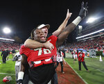FILE - In this Nov. 23, 2019, file photo, Georgia coach Kirby Smart jumps onto the back of offensive lineman Isaiah Wilson to celebrate the team's 19-13 win over Texas A&M in an NCAA college football game in Athens, Ga. The Tennessee Titans selected Wilson in the first round of the NFL draft Thursday, April 23, 2020. (Curtis Compton/Atlanta Journal-Constitution via AP, File)