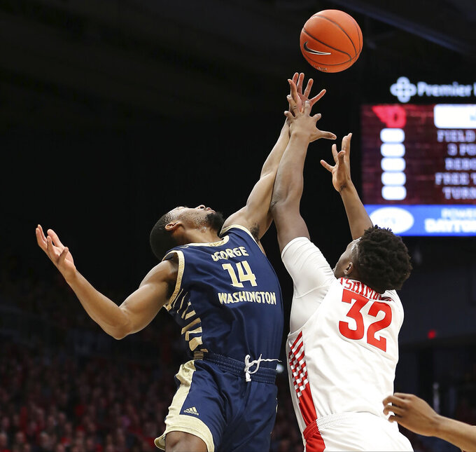 George Washington 's Maceo Jack (14) battles Dayton's Jordy Tshnimanga (32) for a rebound during the first half of an NCAA college basketball game Saturday, March 7, 2020, in Dayton, Ohio. (AP Photo/Tony Tribble)
