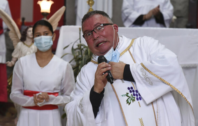 """Sergio Valverde Espinoza, a Catholic priest of the Cristo Rey church who modified a popular song called """"Sopa de Caracol,"""" or Snail Soup in English, gestures during a Mass in San Jose, Costa Rica, Sunday, May 2, 2021. Valverde changed the song's lyrics to a message calling for the use of face masks and care during the pandemic. (AP Photo/Carlos Gonzalez)"""