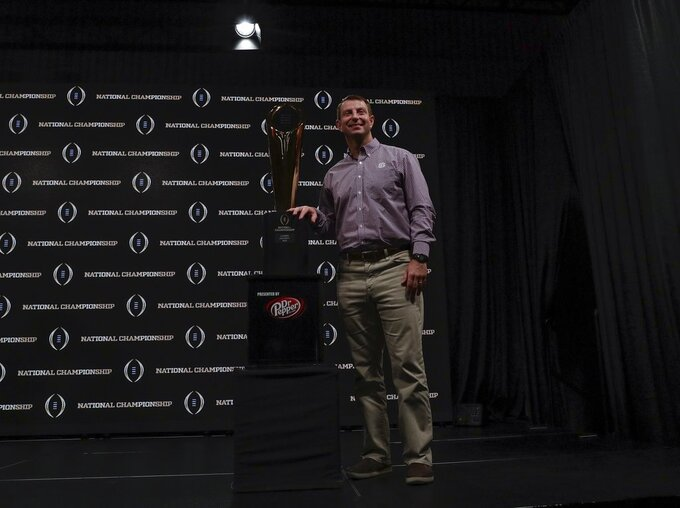 Clemson head coach Dabo Swinney poses with the championship trophy at a news conference for the NCAA college football playoff championship game Tuesday, Jan. 8, 2019, in San Jose, Calif. (AP Photo/David J. Phillip)