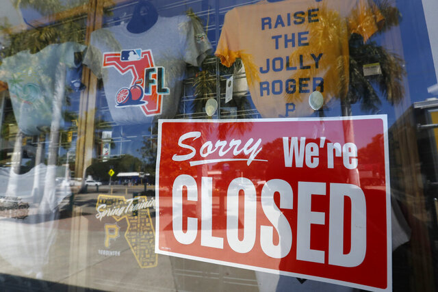 A closed sign is displayed on the Pittsburgh Pirates spring training baseball gift shop at LECOM Park, Monday, March 16, 2020, in Bradenton, Fla. Major League Baseball has delayed the start of its season by at least two weeks because of the coronavirus outbreak and suspended the rest of its spring training schedule. (AP Photo/Carlos Osorio)
