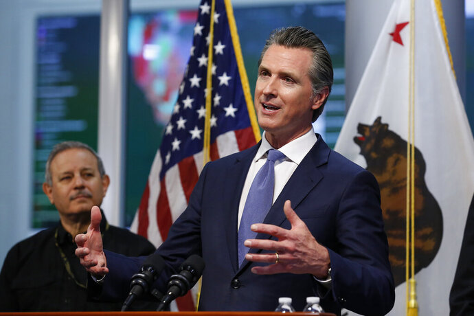 FILE - California Gov. Gavin Newsom gives an update to the state's response to the coronavirus, at the Governor's Office of Emergency Services in Rancho Cordova Calif., Tuesday, March 17, 2020. At left is Mark Ghilarducci, director of the California Office of Emergency Services, OES. California is creating roving