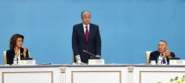 FILE- In this file photo taken on Tuesday, April 23, 2019, Kazakhstan's interim President Kassym-Jomart Tokayev, center, stands as former Kazakh President Nursultan Nazarbayev, right, and Dariga Nazarbayeva, daughter of Kazakhstan's former president Nursultan Nazarbayev, left, applaud to him during the Nur Otan party congress in Nur-Sultan, the capital city of Kazakhstan. Kazakhstan's president on Monday May 4, 2020, put his aide in charge of the country's senate, moving to tighten his grip on power in the energy-rich Central Asian nation. President Kassym-Jomart Tokayev's move follows his decree stripping the daughter of his predecessor of the speaker's job over the weekend. (AP Photo, File)