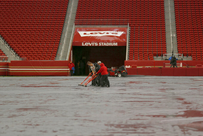 Workers push water off a tarp covering the field from rain at Levi's Stadium before an NFL football game between the San Francisco 49ers and the Indianapolis Colts in Santa Clara, Calif., Sunday, Oct. 24, 2021. A powerful storm roared ashore Sunday in Northern California, flooding highways, toppling trees and causing mud flows as forecasters predict record-breaking rainfall. (AP Photo/Jed Jacobsohn)