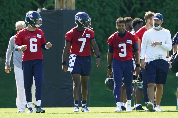 Seattle Seahawks quarterbacks Russell Wilson (3), Geno Smith (7) and Anthony Gordon (6) walk with offensive coordinator Brian Schottenheimer, right, and head coach Pete Carroll, left, following the last day of NFL football training camp, Thursday, Sept. 3, 2020, in Renton, Wash. (AP Photo/Ted S. Warren)