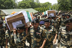 Indian Border Security Force (BSF) officers carry the coffins of four of their colleagues who were killed early Wednesday during a wreath-laying ceremony at the BSF headquarters in Jammu, India, Wednesday, June 13, 2018. Indian and Pakistani forces fired along the highly militarized frontier in disputed Kashmir early Wednesday after Pakistani firing killed at least four Indian paramilitary soldiers and injured three others on border patrol, Indian officials said. (AP Photo/Channi Anand)
