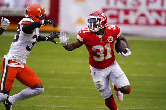 Kansas City Chiefs running back Darrel Williams (31) runs from Cleveland Browns cornerback Terrance Mitchell, left, during the second half of an NFL divisional round football game, Sunday, Jan. 17, 2021, in Kansas City. (AP Photo/Jeff Roberson)