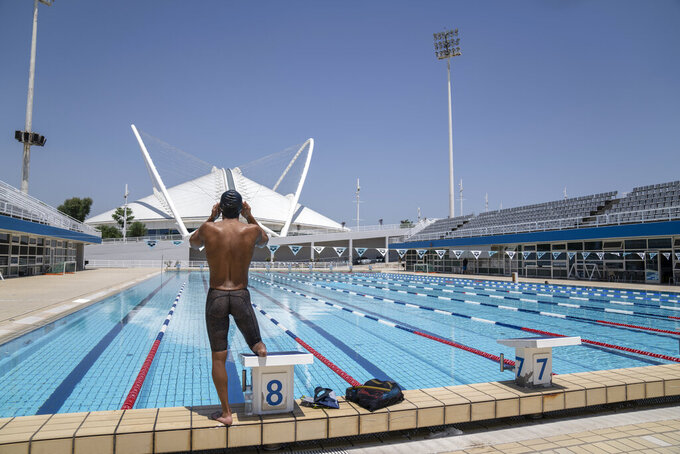 Syrian refugee Ibrahim al-Hussein, an amputee swimmer who lost his leg during the war in Syria, prepares to dive during a training at the Olympic Aquatic Centre, in Athens, on Wednesday , June 30, 2021. Ibrahim al-Hussein will be part of a Refugee Paralympic Team for the Tokyo 2020 Paralympic Games as the International Paralympic Committee announce Wednesday. (AP Photo/Petros Giannakouris)