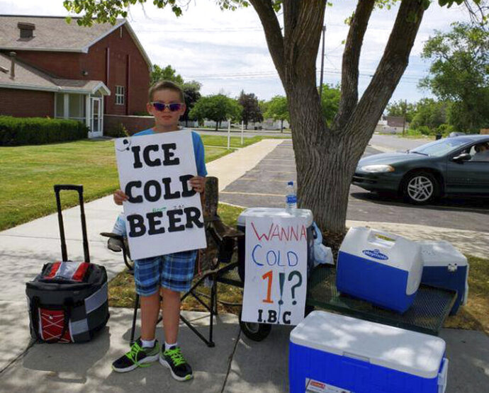In this Tuesday, July 16, 2019 photo provided by the Brigham City Police Department, Seth Parker stands at his soda stand in Brigham City, Utah. Parker is earning widespread social media attention for his neighborhood soda stand thanks to a sign he holds that reads,