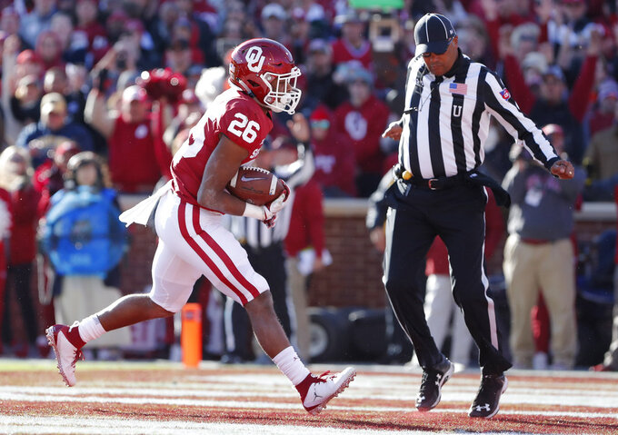 Oklahoma running back Kennedy Brooks (26) runs in for a touchdown against Oklahoma State in the first half of an NCAA college football game in Norman, Okla., Saturday, Nov. 10, 2018. (AP Photo/Alonzo Adams)