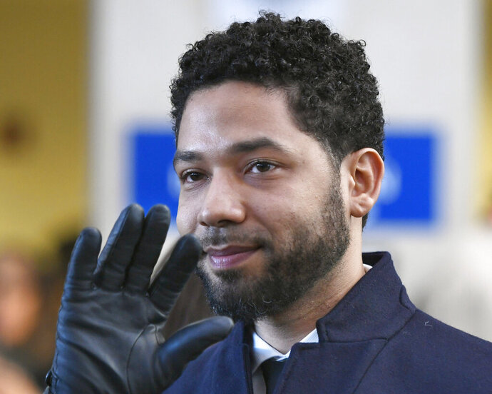 FILE - In this March 26, 2019, file photo, actor Jussie Smollett waves as he leaves Cook County Court after his charges were dropped in Chicago. A judge in Chicago has ordered the file in the Smollett criminal case unsealed. Cook County Judge Steven Watkins said Thursday, May 23, 2019, that while there are good arguments in favor of keeping the file sealed, the