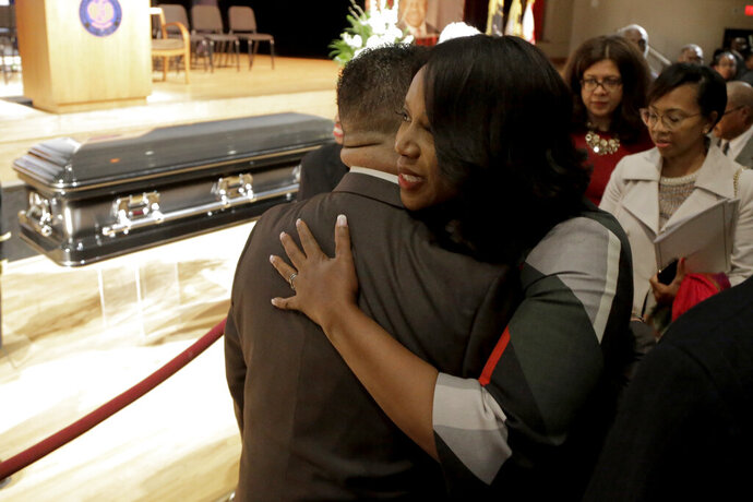 Maya Rockeymoore, right, widow of U.S. Rep. Elijah Cummings, hugs a supporter near the casket containing the body of her husband during a viewing service at Morgan State University, Wednesday, Oct. 23, 2019, in Baltimore. The Maryland congressman and civil rights champion died Thursday, Oct. 17, at age 68 of complications from long-standing health issues. (AP Photo/Julio Cortez)