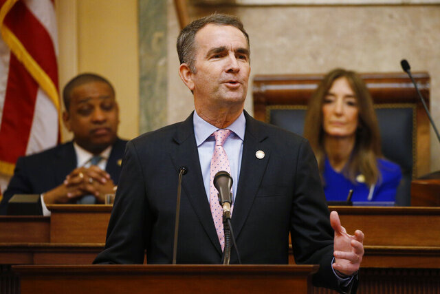 FILE - In this Jan. 8, 2020, file photo, Virginia Gov. Ralph Northam, center, gestures as he delivers his State of the Commonwealth address as House Speaker Eileen Filler-Corn, D-Fairfax, right, and Lt. Gov. Justin Fairfax, left, listen before a joint session of the Virginia Assembly at the state Capitol in Richmond, Va. Northam plans to declare a temporary emergency Wednesday, Jan. 15, banning all weapons, including guns, from Capitol Square ahead of a massive rally planned next week over gun rights. (AP Photo/Steve Helber, File)