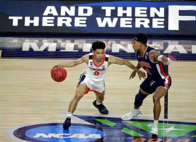 Virginia guard Kihei Clark, left, drives past Auburn guard Bryce Brown during the first half in the semifinals of the Final Four NCAA college basketball tournament, Saturday, April 6, 2019, in Minneapolis. (AP Photo/Matt York)