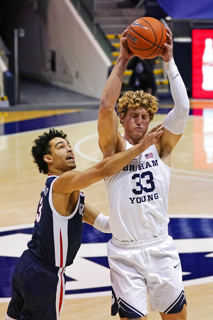 Gonzaga guard Andrew Nembhard, left, defends against BYU forward Caleb Lohner (33) in the first half during an NCAA college basketball game Monday, Feb. 8, 2021, in Provo, Utah. (AP Photo/Rick Bowmer)