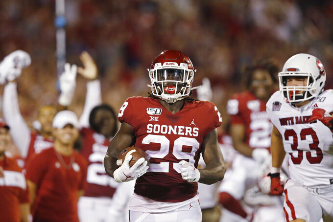 Oklahoma running back Rhamondre Stevenson (29) carries the ball in for a touchdown in front of South Dakota linebacker Jake Matthew (33) in the third quarter of an NCAA college football game Saturday, Sept. 7, 2019, in Norman, Okla. (AP Photo/Sue Ogrocki)