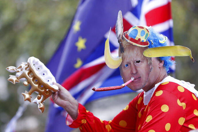 An anti Brexit demonstrator wears a mask depicting Britain's prime minister Boris Johnson protests outside the Cabinet office in London, Thursday, Aug. 29, 2019. Political opposition to Prime Minister Boris Johnson's move to suspend Parliament is crystalizing, with protests around Britain and a petition to block the move gaining more than 1 million signatures. (AP Photo/Alastair Grant)