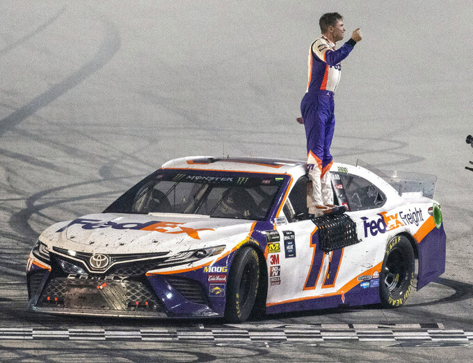 Denny Hamlin celebrates after winning the Bass Pro Shops NRA Night Race at Bristol Motor Speedway, Saturday, Aug. 17, 2019, in Bristol Tenn. (Andre Teague/Bristol Herald Courier via AP)